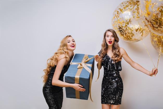 Gelukkige verjaardag geweldige feesttijd van twee charmante grappige jonge vrouwen. zwarte luxe jurken, elegante uitstraling, lang krullend haar, plezier maken, cadeau, ballonnen, positiviteit uitdrukken. Gratis Foto
