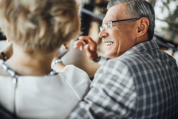 Gelukkige verjaardag. grijsharige man die gelukkig lacht terwijl hij zijn kortharige vrouw knuffelt Premium Foto