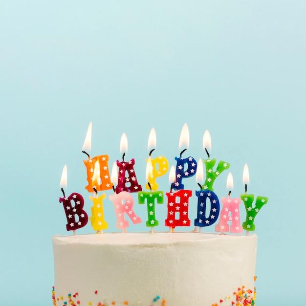 Gelukkige verjaardagskaarsen over de cake tegen blauwe achtergrond Gratis Foto