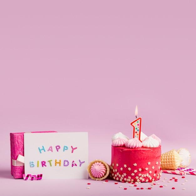 Gelukkige verjaardagskaart dichtbij de cake met aangestoken kaarsen en giftdoos op purpere achtergrond Gratis Foto