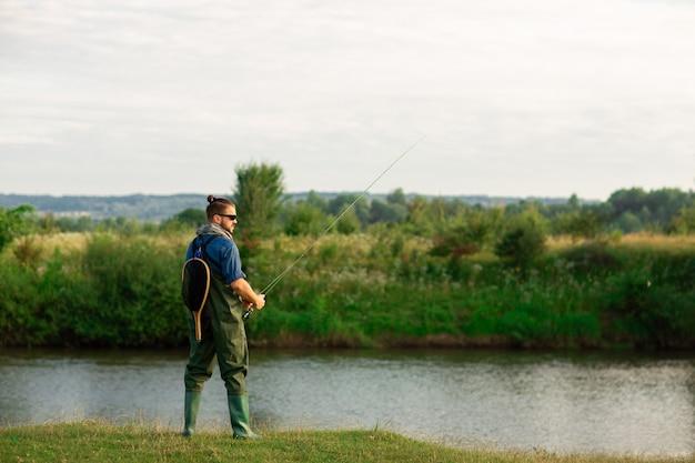 Gelukkige visser met speciaal kostuum en hengel dichtbij aan de rivier Premium Foto