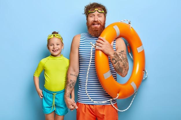 Gelukkige vriendelijke vader en dochter klaar om te zwemmen, koele zomervakantie samen doorbrengen, bril dragen, oranje reddingsboei vasthouden, casual t-shirts en korte broeken dragen, handen vasthouden, geïsoleerd op blauwe muur Gratis Foto