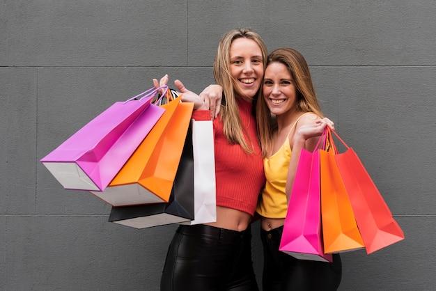 Gelukkige vrienden die boodschappentassen houden Gratis Foto