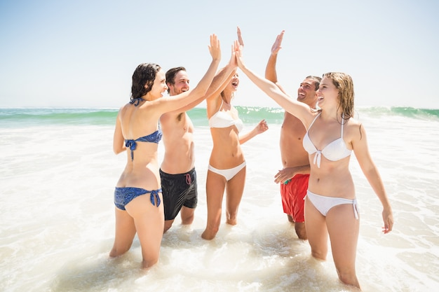Gelukkige vrienden die een hoogte vijf op het strand geven Premium Foto