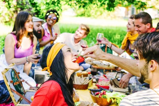 Gelukkige vrienden die een picknick in de tuin maken openlucht Premium Foto