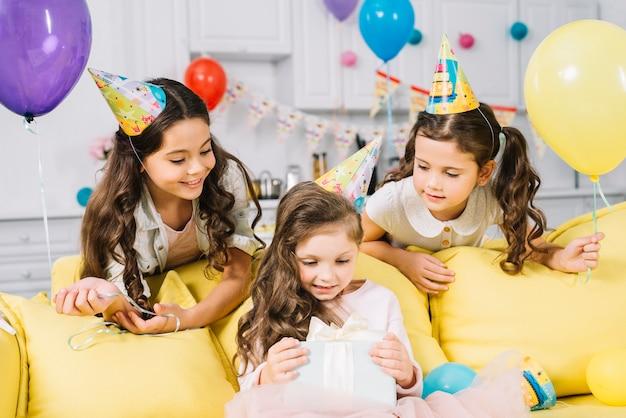 Gelukkige vrienden die feestvarken bekijken die het heden thuis openen Gratis Foto