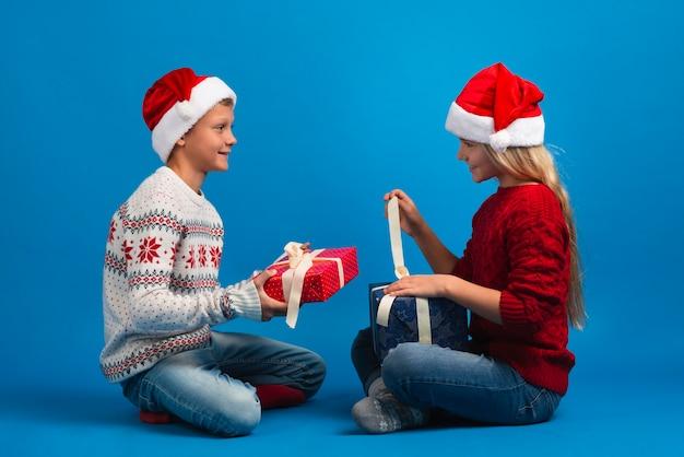 Gelukkige vrienden die kerstmisgiften uitpakken Gratis Foto
