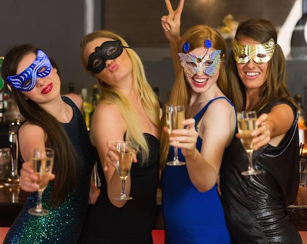 Gelukkige vrienden die maskers dragen die champagneglazen tonen Premium Foto