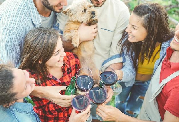 Gelukkige vrienden die met glazen rode wijn toejuichen openlucht Premium Foto