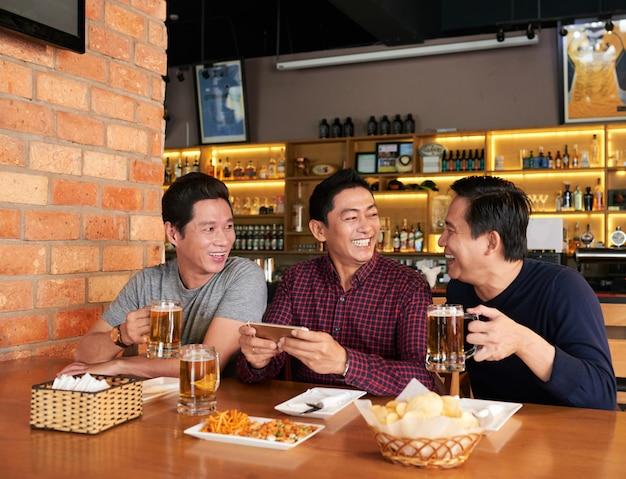 Gelukkige vrienden die tijd samen doorbrengen in een bierbar Gratis Foto