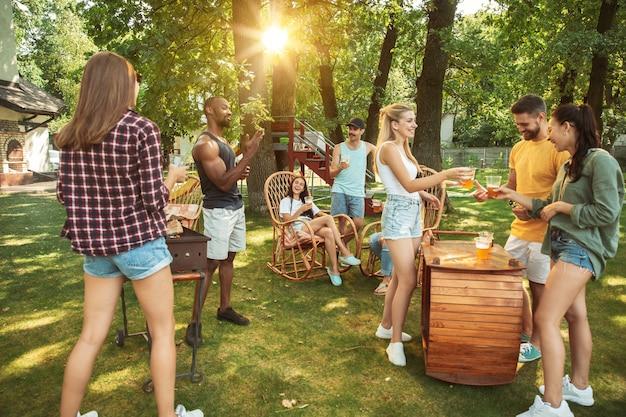 Gelukkige vrienden hebben bier en barbecue feest op zonnige dag Gratis Foto