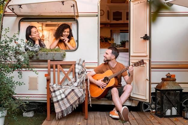 Gelukkige vrienden in een busje spelen en zingen Premium Foto