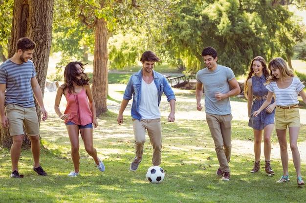 Gelukkige vrienden in het park met voetbal Premium Foto