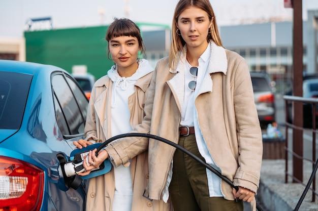 Gelukkige vrienden tanken auto in benzinestation. vakantiereis van vrienden Gratis Foto