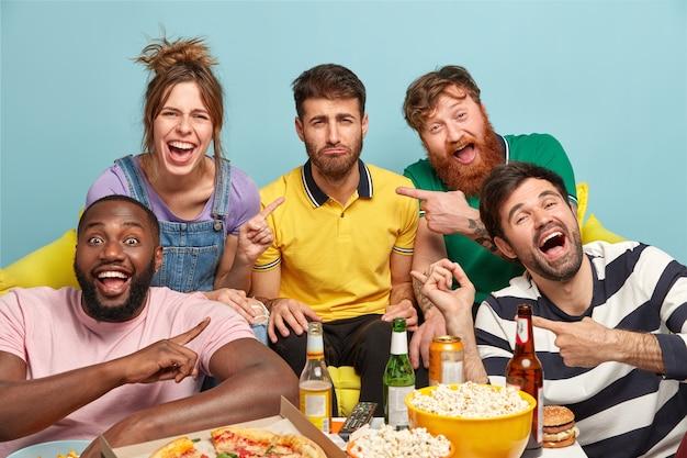 Gelukkige vrienden wijzen naar een ongelukkige, bebaarde man die niet gretig is om naar komedie te kijken, uit zijn ontevredenheid. vijf multi-etnische jongeren eten een lekker hapje en drinken koud bier terwijl ze stream-tv kijken Gratis Foto