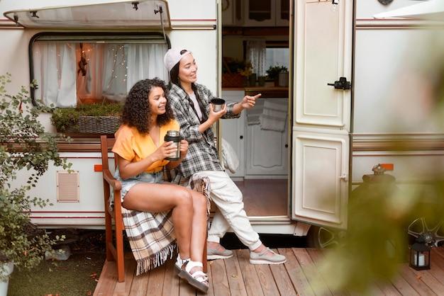 Gelukkige vriendinnen en camper Gratis Foto