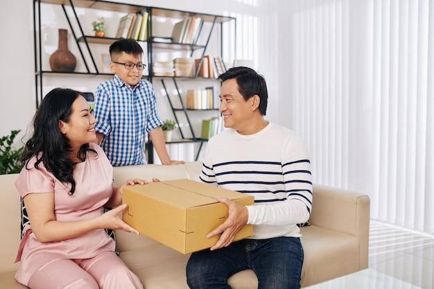 Gelukkige vrij aziatische vrouw die verjaardagsgeschenk van echtgenoot en zoon ontvangt Premium Foto