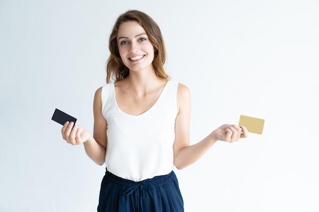 Gelukkige vrij jonge vrouw die twee plastic kaarten houdt Gratis Foto