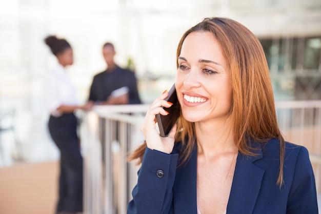 Gelukkige vrolijke bedrijfsdame die op cellphone spreekt Gratis Foto