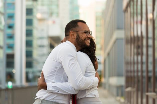 Gelukkige vrolijke bedrijfsmens die vrouwelijke vriend koestert Gratis Foto