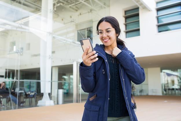 Gelukkige vrolijke bureauwerknemer die online app gebruiken Gratis Foto