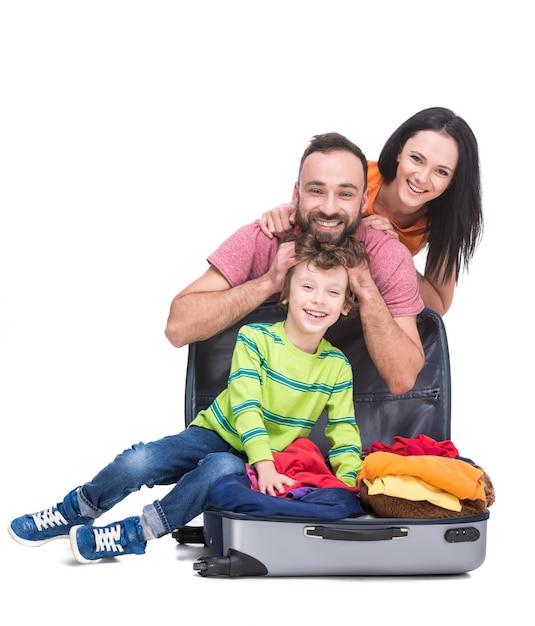 Gelukkige vrolijke ouders en hun zoon in een koffer. Premium Foto