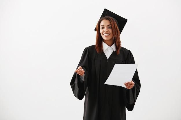 Gelukkige vrolijke vrouw gediplomeerde het glimlachen holdingstest over witte oppervlakte Gratis Foto