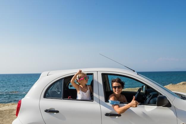 Gelukkige vrolijke vrouw met dochter die zich in auto met uitgestrekte wapens bevinden en camera bekijken. ontspannen in een auto. reis met auto. gelukkig jong vrouwen en kind die van vrijheid op roadtrip vakantie genieten. Premium Foto