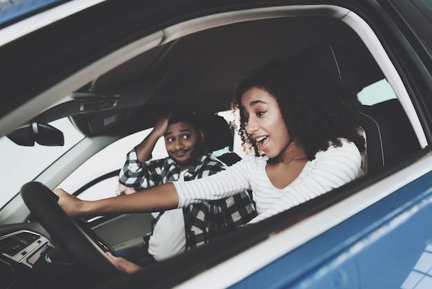 Gelukkige vrouw bij stuurwiel geschokte passagier. Premium Foto
