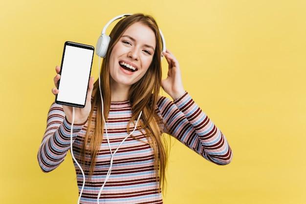 Gelukkige vrouw die aan muziek op telefoonmodel luistert Gratis Foto