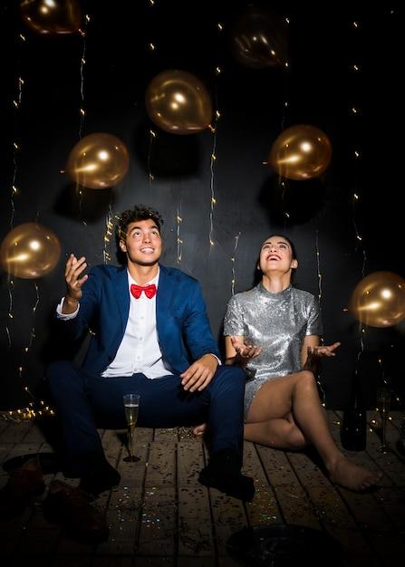 Gelukkige vrouw die dichtbij de mens tussen het werpen van ballons glimlachen Gratis Foto