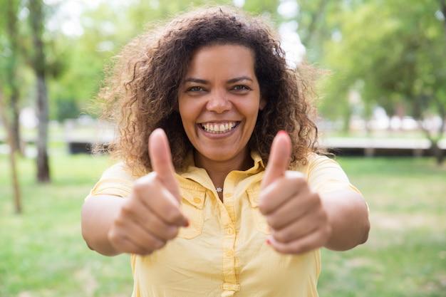 Gelukkige vrouw die duimen tonen en bij camera in park stellen Gratis Foto
