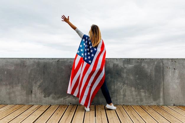 Gelukkige vrouw die een amerikaanse vlag houdt Premium Foto