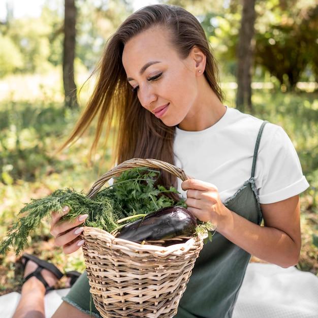 Gelukkige vrouw die een picknick met gezonde snacks heeft Premium Foto