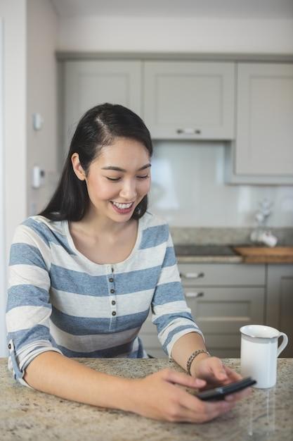 Gelukkige vrouw die een tekstbericht op haar mobiele telefoon in keuken typt Premium Foto