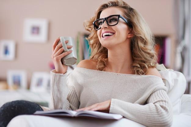 Gelukkige vrouw die een tijdschrift leest en koffie drinkt Gratis Foto