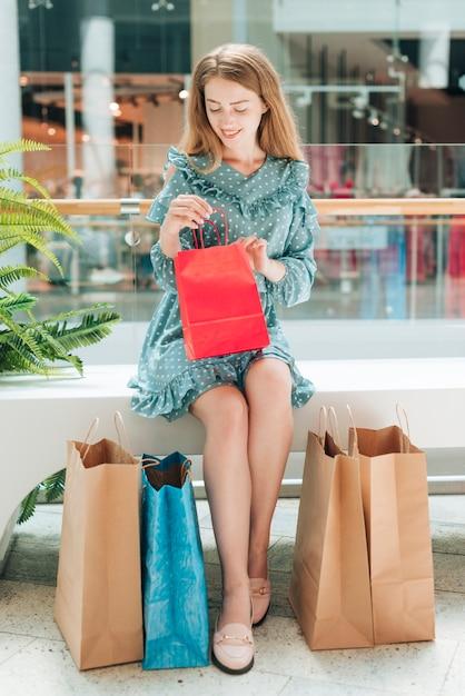Gelukkige vrouw die één van haar zakken controleert Gratis Foto