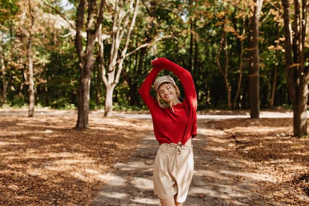 Gelukkige vrouw die geweldige tijd heeft in het de herfstpark. glimlachend blonde poseren tussen gevallen bladeren. Gratis Foto