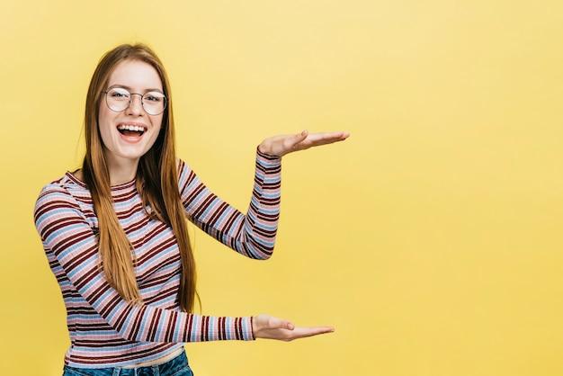 Gelukkige vrouw die glazen met exemplaarruimte draagt Gratis Foto
