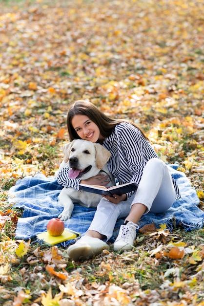 Gelukkige vrouw die haar hond koestert Gratis Foto