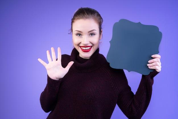 Gelukkige vrouw die haar vijf vingers en een marineblauw karton toont Gratis Foto