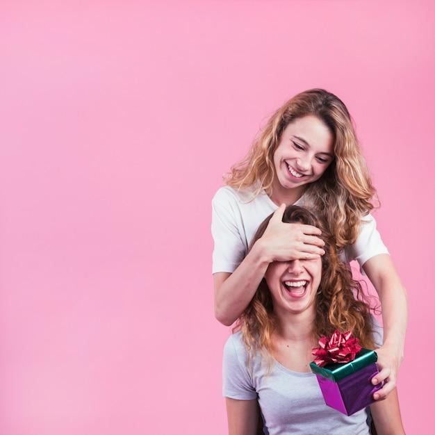 Gelukkige vrouw die haar vrouwelijke ogen behandelen die giftdoos houden tegen roze achtergrond Gratis Foto