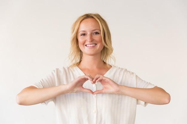 Gelukkige vrouw die het gebaar van het handhart tonen Gratis Foto