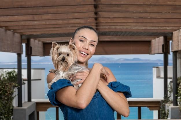 Gelukkige vrouw die hond op terras omhelst Premium Foto