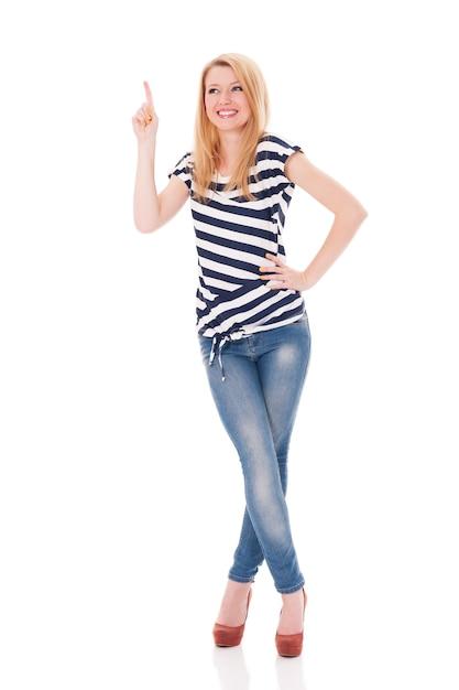 Gelukkige vrouw die in gestreepte blouse op copyspace richt Gratis Foto