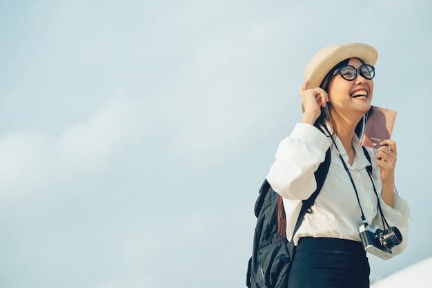 Gelukkige vrouw die met camera en paspoort op reis per vliegtuig wachten. Premium Foto