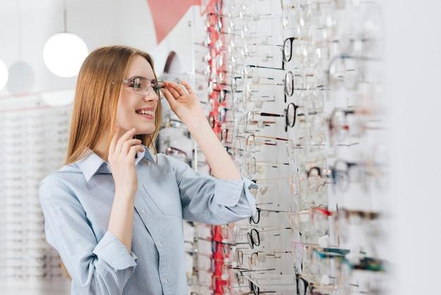 Gelukkige vrouw die nieuwe glazen zoekt bij optometrist Premium Foto
