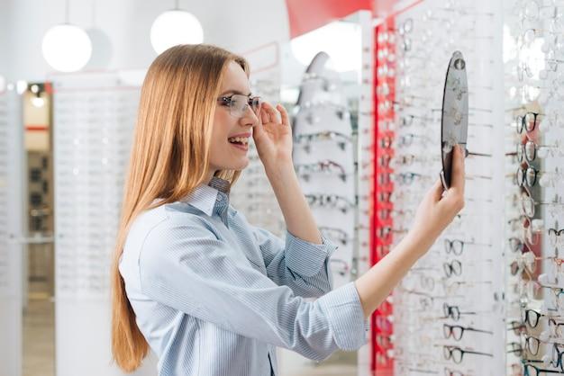 Gelukkige vrouw die nieuwe glazen zoekt bij optometrist Gratis Foto
