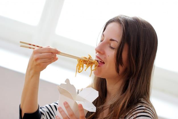 Gelukkige vrouw die noedels eet Gratis Foto