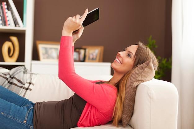 Gelukkige vrouw die op bank ligt en digitale tablet gebruikt Gratis Foto